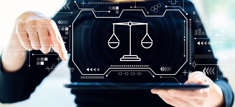 Imagen de unas manos con una infografía de la balanza de la justicia sobre un ordenador