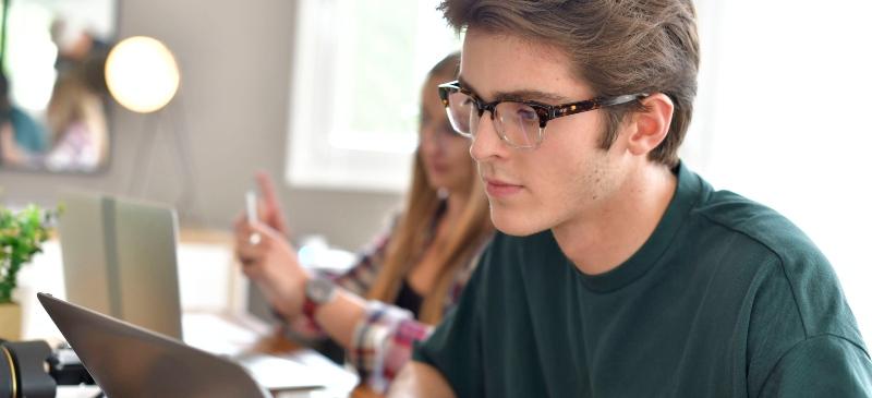 Joven estudiante ante un ordenador y una chica al fondo