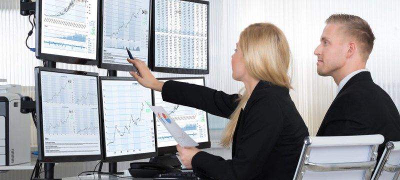 Un hombre y una mujer analizando datos en varias pantallas de ordenador.