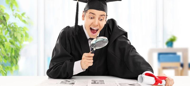Chico sorprendido buscando una oferta de trabajo en el periódico vestido con toga y virrete