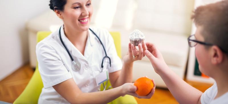 Nutricionista dando una manzana a un niño obeso y retirándole un pastel