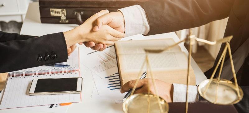 dos manos que se estrechan con elementos de derecho como una balanza y un empresario, como un teléfono móvil