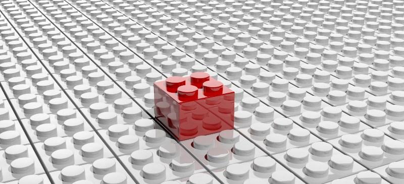 Ficha de lego roja sobre una placa blanca de fichas lego