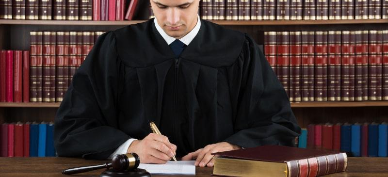 Abogado en una biblioteca escribiendo un informe a mano con un libro de derecho a su lado