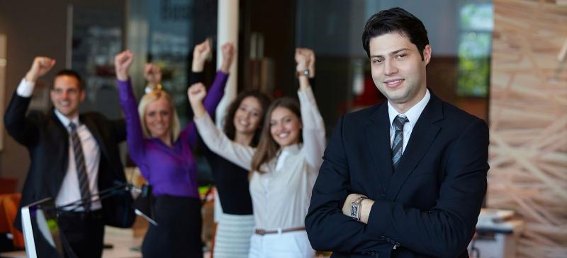 Persona que mira al espectador mientras detrás un grupo levanta los brazos en señal de triunfo