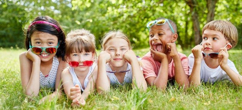 Cinco niños de distintas razas en actitud sonriente tumbados en la hierba frente a la cámara