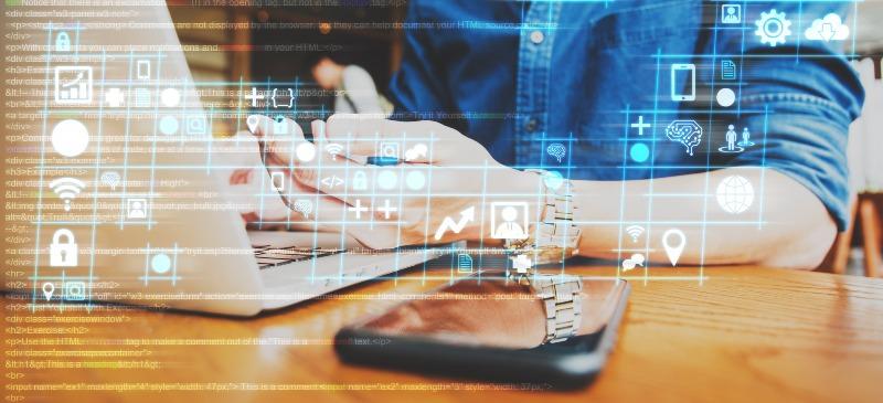 Manos sobre un teclado de ordenador y con una tablet en primer plano