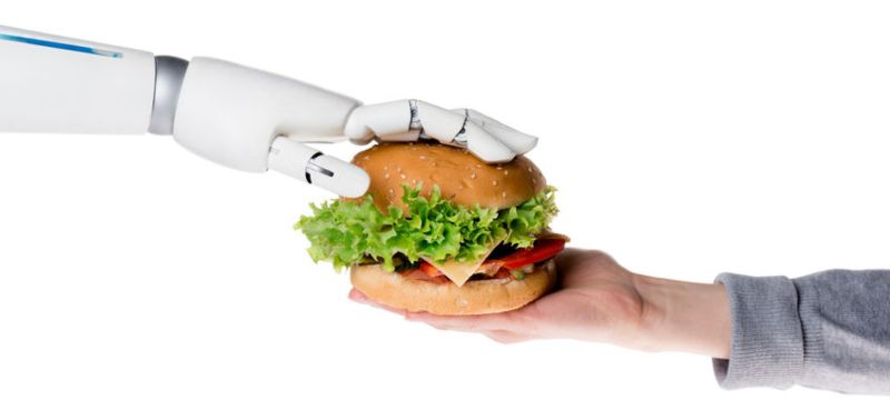 Mano robótica entrega hamburguesa a mano humana.