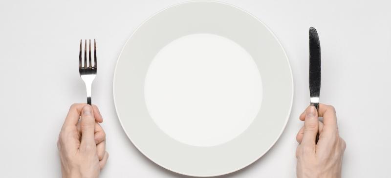 Imagen de un plato vacío y dos manos con cubiertos.