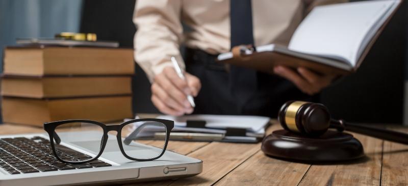 Imagen de una mesa en la que además de un mazo de justicia hay unas gafas y un ordenador abierto