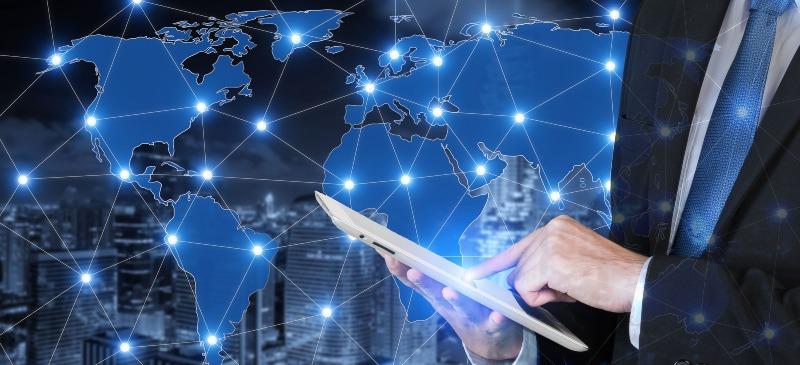 persona que está con una tablet y de fondo tiene un mapa del mundo en digital, conectado con puntos de luz.