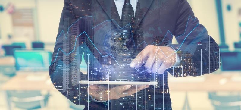 Hombre con traje con una tableta que analiza en infografía datos de la bolsa