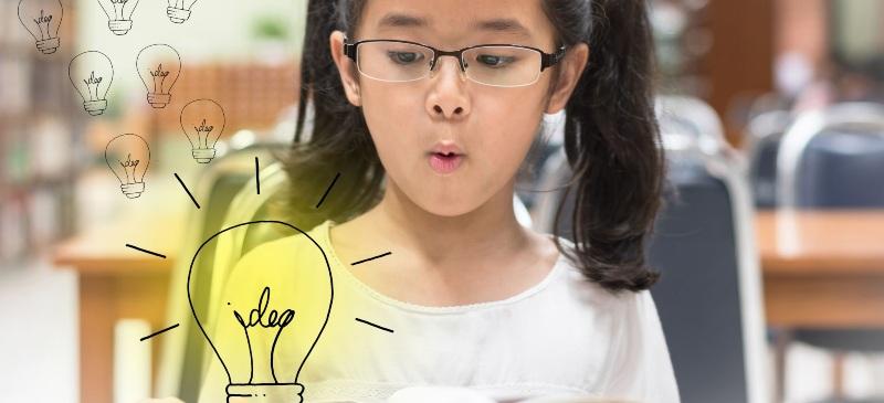 Niña con cara de asombro ante unas bombillas dibujadas en la imagen