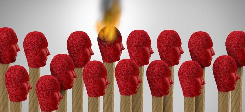 Síndrome de Burnout. una cerilla con cabeza humana se enciende alrededor de otras cerillas