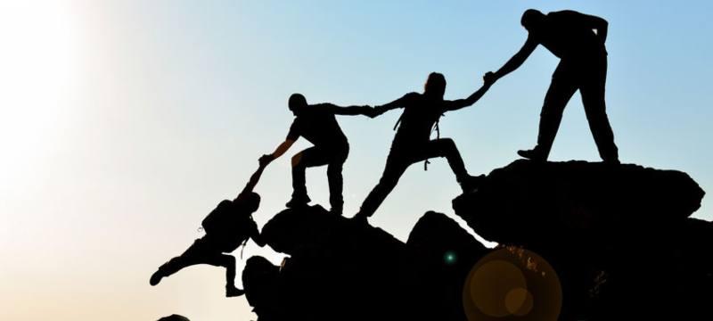 Un grupo de personas ayudándose para subir una montaña