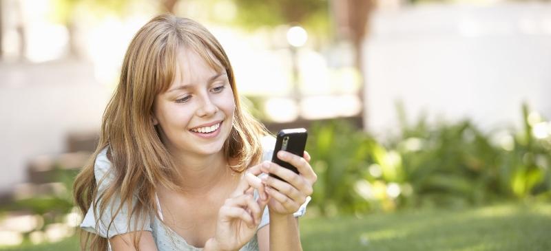 chica con teléfono tumbada en la hierba