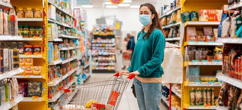chica con mascarilla en el supermercado con un carrito de la compra