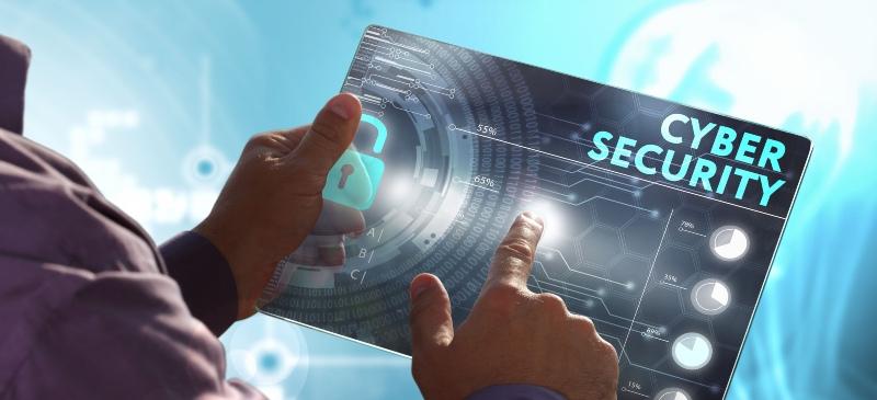 Imagen de alguien con una tablet y la palabra ciberseguridad en un holograma