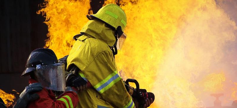 Incendios y protección. Dos bomberos apagando un fuego.