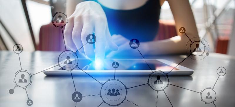 Imagen de una mano que toca una tablet de la que salen elementos relacionados con community manager