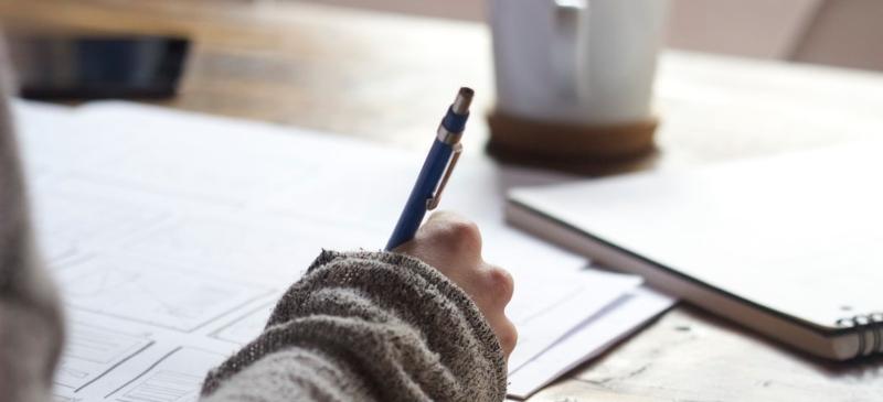 Mano que escribe sobre unos papeles en una mesa con una taza de café