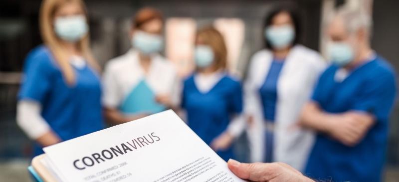 imagen de un equipo médico al fondo y en primer plano un texto con la palabra coronavirus