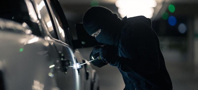 Un ladrón intentando robar un coche