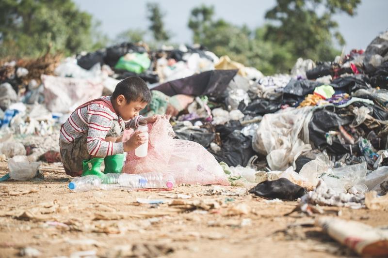 Niño en un basurero recogiendo algo del suelo