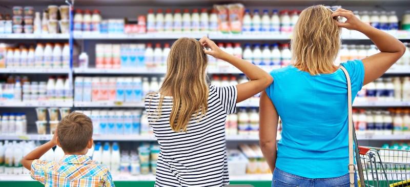 Una madre y sus dos hijos frente a un lineal de lácteos en el supermercado