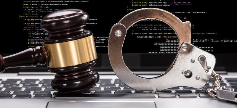 Maza de juez y esposas sobre un teclado de ordenador