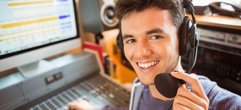 Chico que mira a la cámara que autoedita un programa de radio