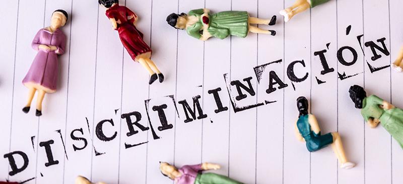 Imagen de la palabra discriminación con figuras de muñecos mutilados