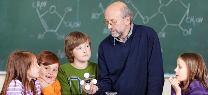 profesor explicando ciencia en una clase a niños