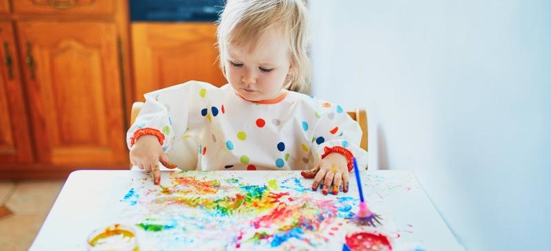 Los niños, el juego y el arte. Niña jugando con pintura de dedos en una mesa, con la cara manchada.