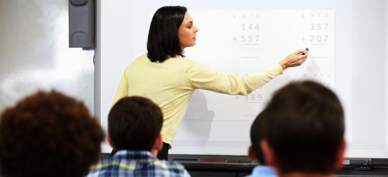 profesora de matemáticas ante una pizarra digital en clase