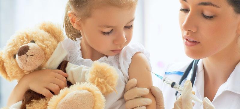 Vacunación de una niña con su osito de peluche y una enfermera que administra vacunas.