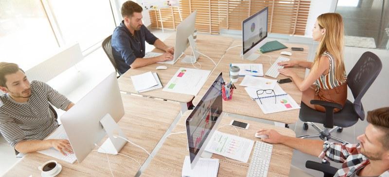 Empresa de varios trabajadores sentados alrededor de una mesa con sus ordenadores