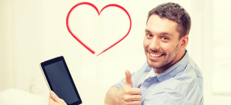 chico sentado en un sofá con una tableta en la mano y un corazón de fondo; tiene el pulgar hacia arriba y sonrie