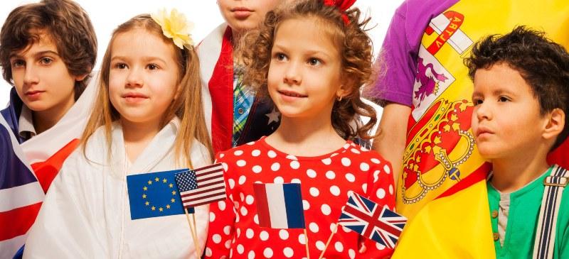 Niños de primaria con una banderita en la mano, símbolo del aprendizaje de idiomas