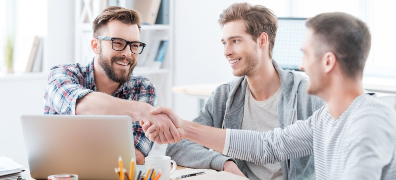 Felicidad en el trabajo. Dos personas sonriendo y dándose la mano.