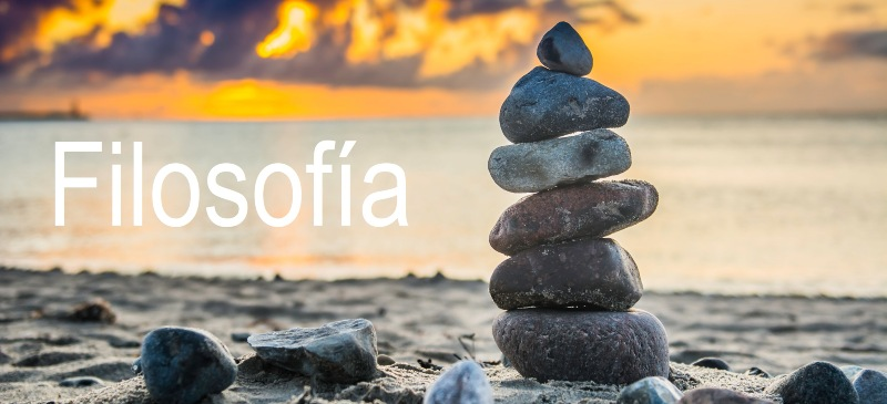 Una playa al amanecer con piedras unas sobre otras y la palabra filosofía, metáfora del equilibrio del ser