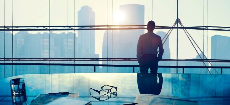 Hombre mirando hacia la ciudad en su despacho desde una cristalera.