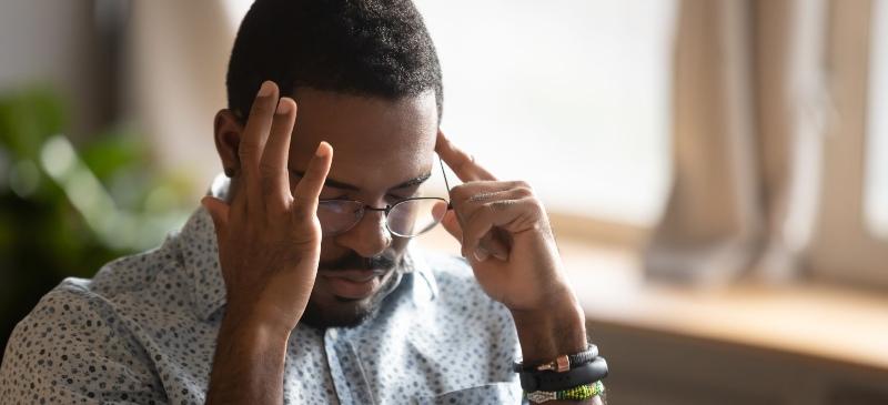 Imagen de un hombre tocándose las sientes, como pensando.