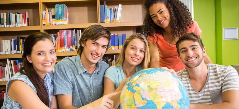Grupo de chicos y chicas en la biblioteca señalando una bola del mundo sobre una mesa