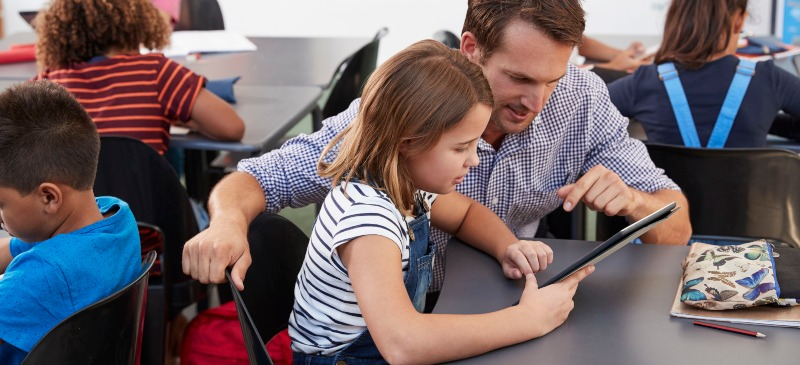 Profesor explica a una alumna algo sobre una tablet