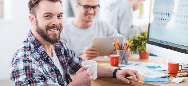 chico con una taza de café frente al ordenador con otra persona detrás, trabajando en una oficina