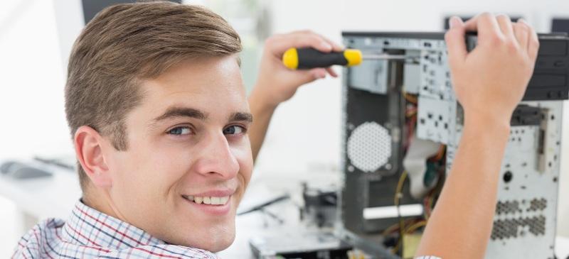 Chico con un destornillador en la parte posterior de un ordenador y mirando a la cámara