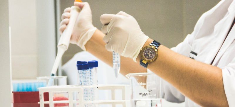 Manos en un laboratorio con pipetas trabajando