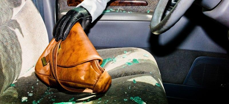 ladrón de bolso. Una mano recoge rompe una ventanilla de un coche y recoge un bolso de un asiento