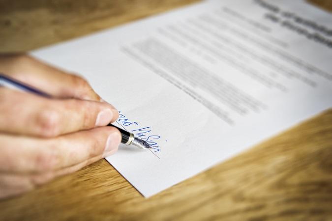 Mano firmando un contrato de trabajo